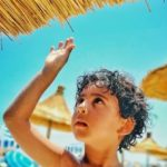 頭への日差しを手で遮る子供
